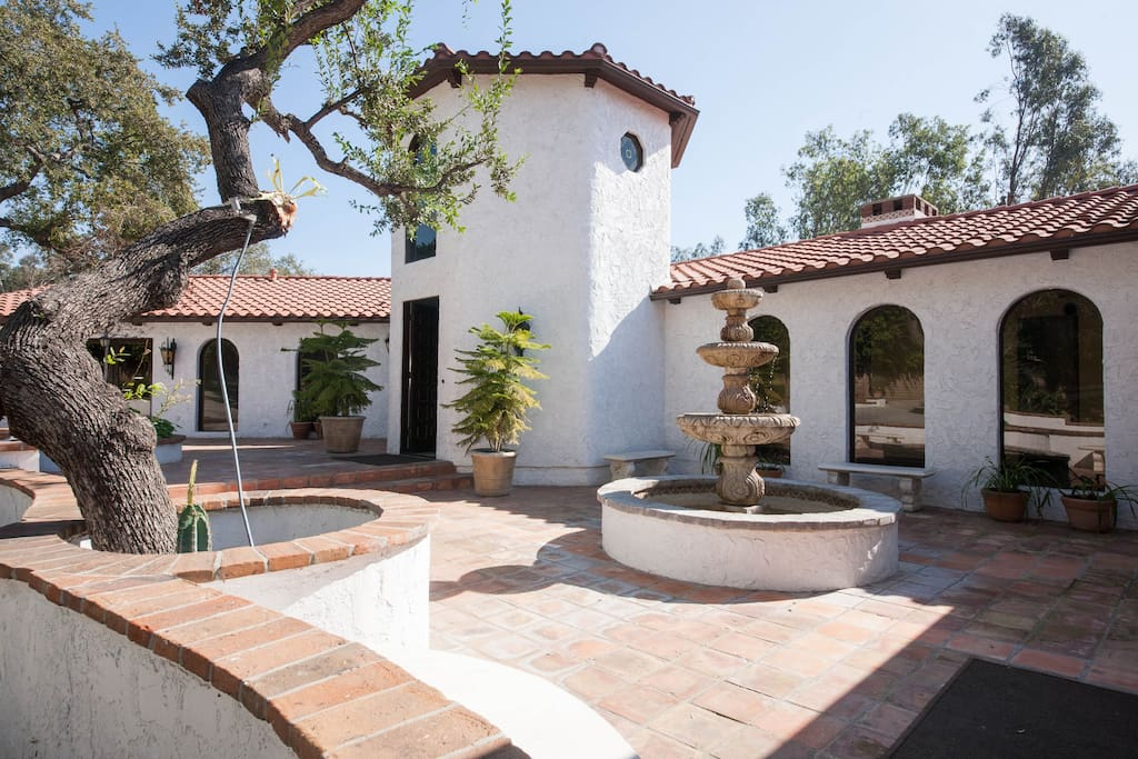 Terra-Cotta court yard with a fountain and a mature oak tree.