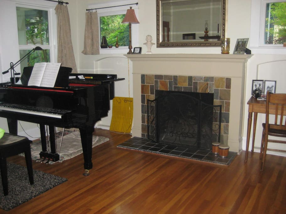 piano in front room with fireplace.