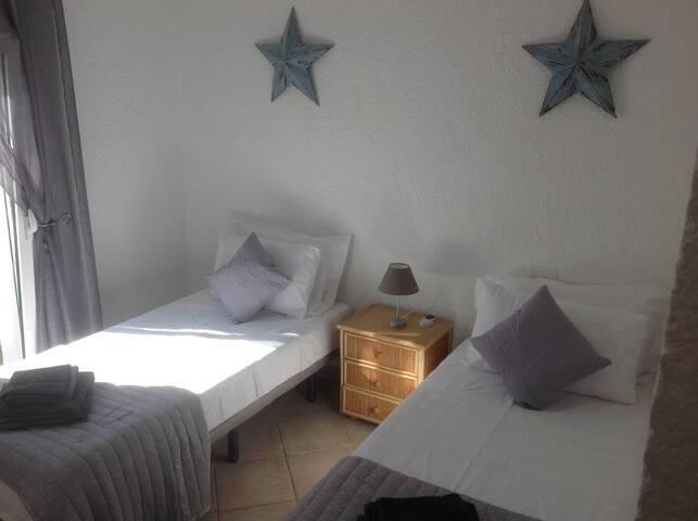 Modern twin bedroom with ceiling fan