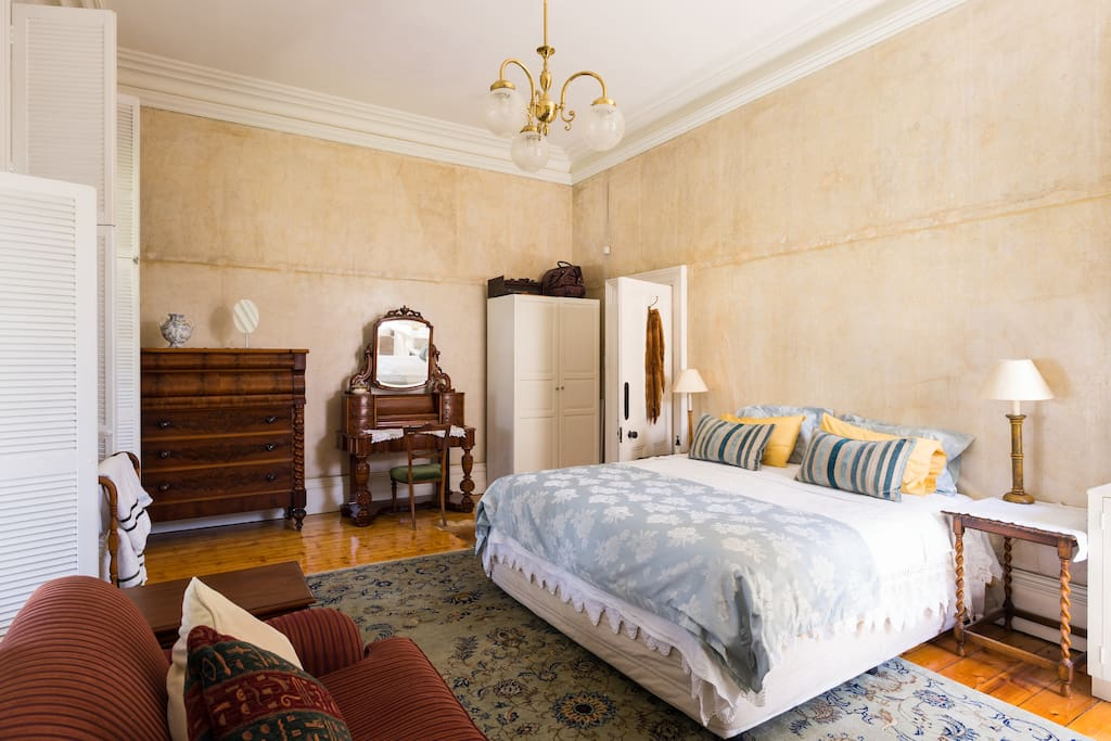 Main bedroom King bed and balcony doors  Leading to the front verandah overlooking a park.Large marble fireplace.