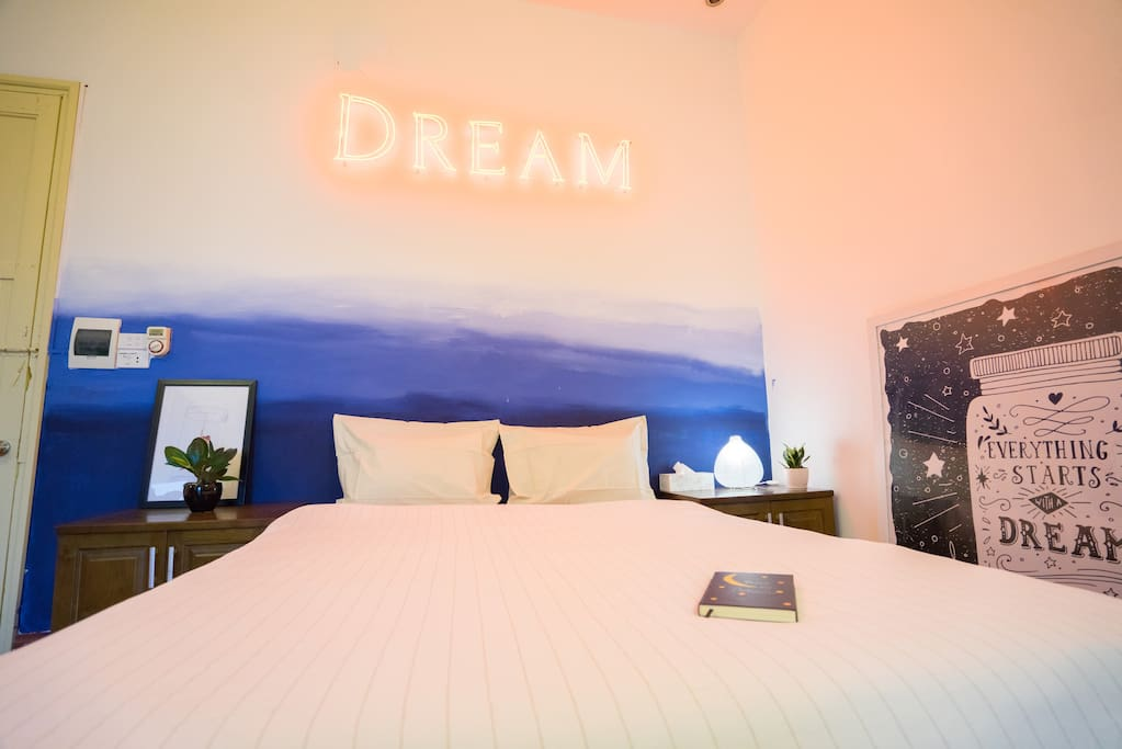 Dreamy bed featuring original neon sign