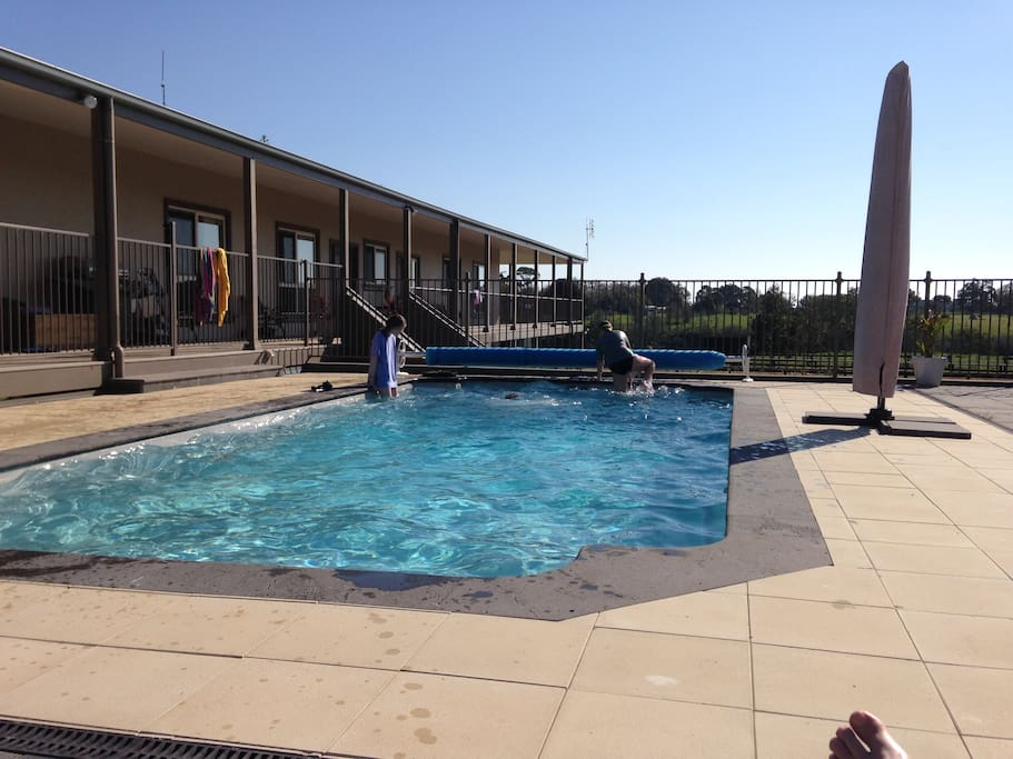 Relax by the heated pool (building seen is not the guesthouse)