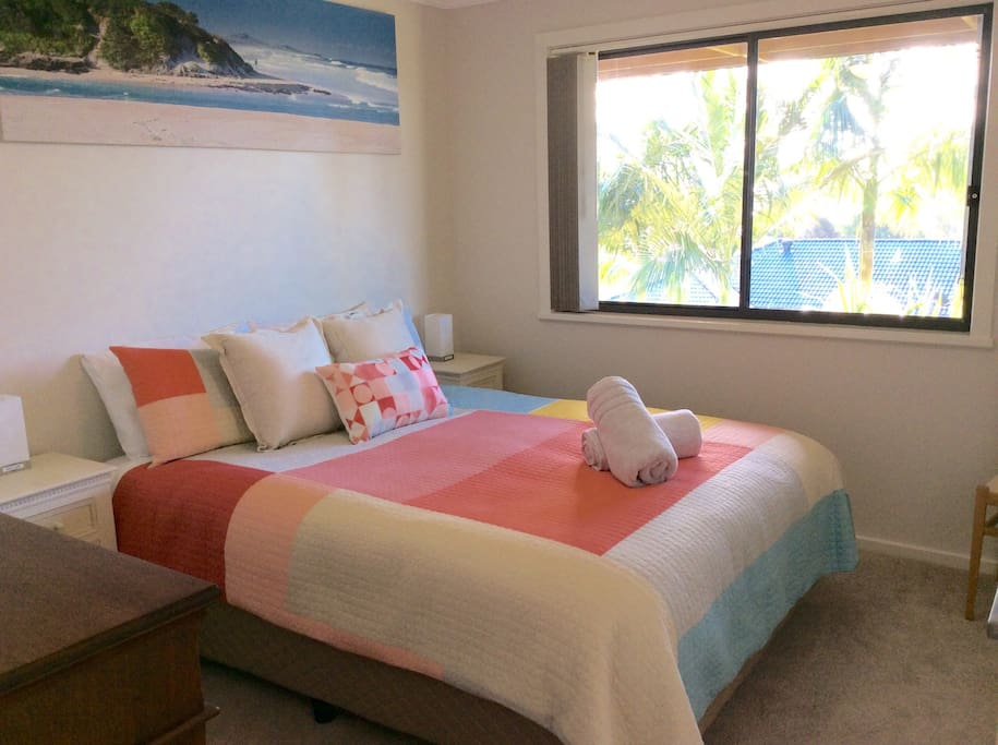 Queen bedroom with bedside tables, air conditioning, wardrobe, hangers, room for luggage.