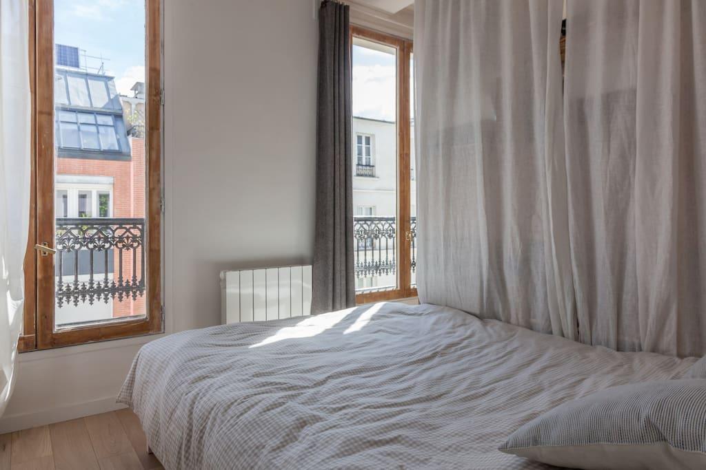 Chambre cocon avec lit double éclairée par une lumière naturelle.