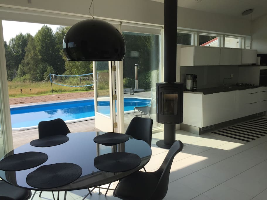 Dining table, kitchen + view to the pool and beach volley court