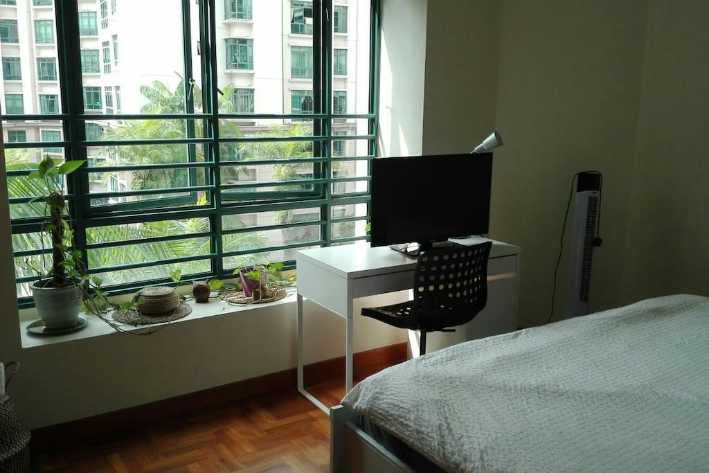 Bedroom with King sized bed and lots of light. View of greenery and pool/ bukit timah hill.