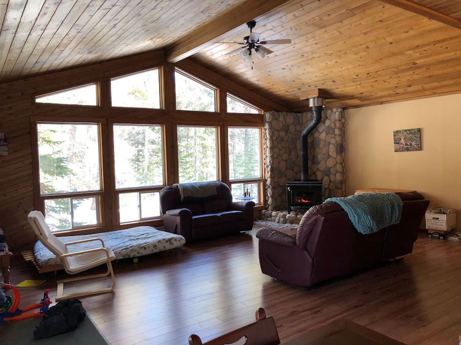 Main Livingroom/family room with sofa, love seat, futon, wood fireplace & small vintage tv. Open concept vaulted ceiling, makes for a beautiful room.