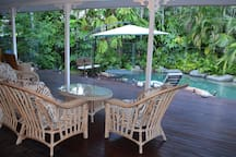 Relax on the back veranda overlooking the pool.