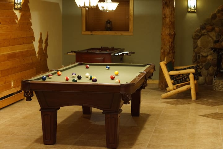 """Our Game Room at the Indian Ridge Lodge is a great place to hang out. Play some foosball, pool, or ping-pong; or just relax on a couch by one of the freestanding stoves. <!-- Check out these reviews!!! -->  """"We had a 3-day family reunion last weekend at Indian Ridge Lodge and it turned out great!   There was plenty of room for everyone to sleep and the accommodations were very clean.  Breakfast is included and it was outstanding both mornings!  (Homemade scones, homemade muffins, ham, sausage, eggs, fruit, homemade jams, milk, juice, homemade granola, etc.)  You certainly won't go away hungry... The game room downstairs was a favorite place for many of the family to hang out but there is also plenty of room upstairs to visit, play card games, etc.   The family who runs the lodge is super nice, accommodating and helpful.  You couldn't ask to meet nicer people. I would HIGHLY recommend Indian Ridge Lodge!""""  <!-- Please note that some breakfast items are seasonal or in limited supply; contact us before your booking with any special requests.-->"""