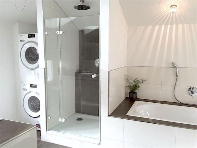 Modernes Badezimmer mit Dusche, Badewanne, washing machine and dryer/ Modern bathroom with shower, bathtub, washing machine and dryer