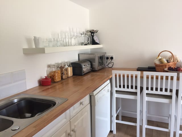 Kitchenette with dishwasher, cooking facilities and 4 bar stools.