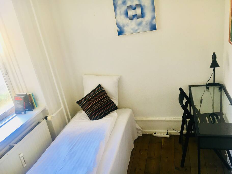 Bedroom 3: a small room with a single bed, overlooks the courtyard behind the building