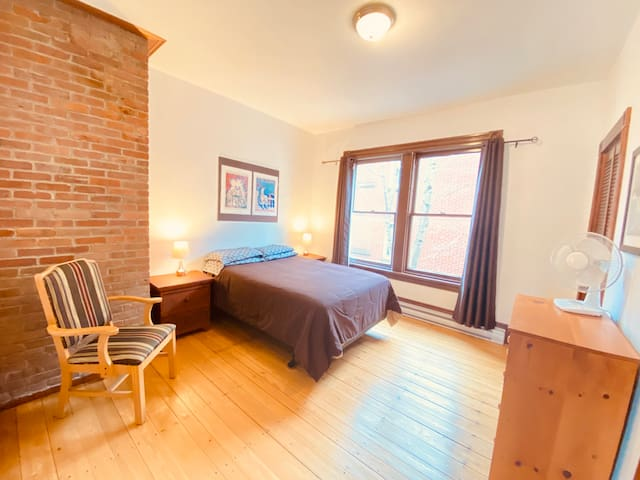 First large bedroom with large windows bathroom with stand up shower off the room