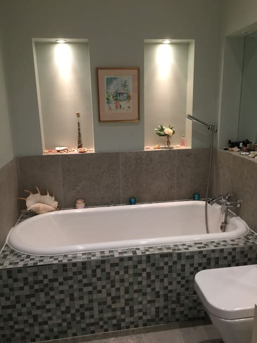 Beautiful, mosaic tiled enclosed bath with atmospheric down lighting with a lovely tiled flooring and heated towel rail