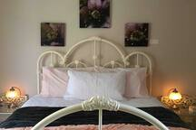 In the beautiful wrought iron bed are soft sheets and electric blankets. Touch lamps illuminate your bedside treats :)