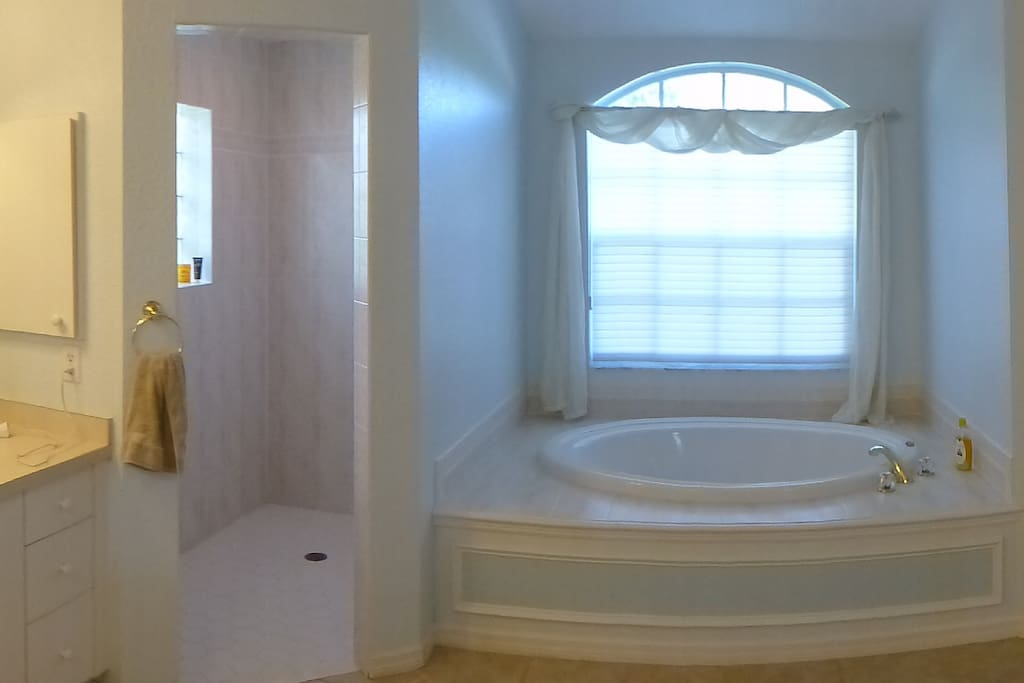 Master bathroom with roman shower, twin vanity units and separate toilet.