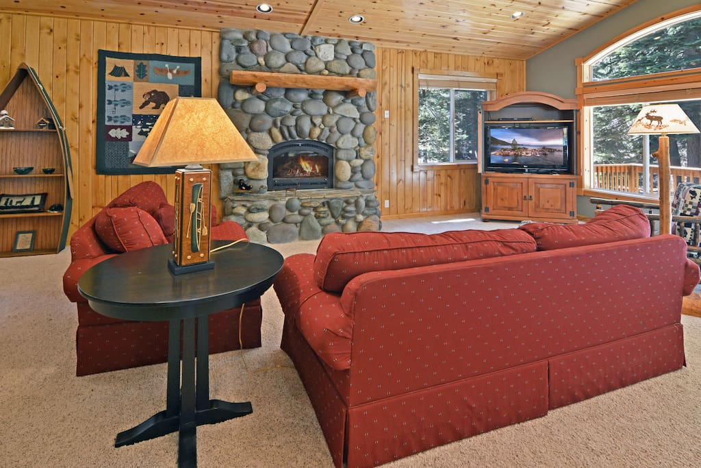 Flat screen TV and stone fireplace in the first living area. Complimentary Wi-Fi is provided.
