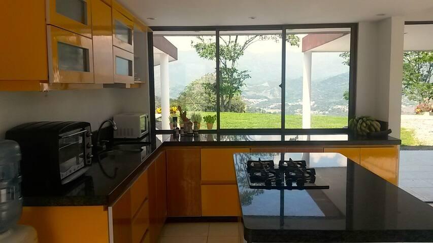 Cocina Integral con ventanal que da frescura y vista a la piscina y el paisaje.