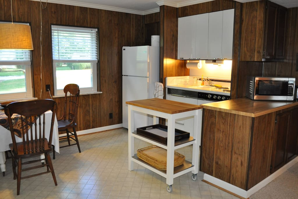 Kitchenette has bar sink next to a 3 burner stove, small oven, full-size refriderator, microwave and toaster.