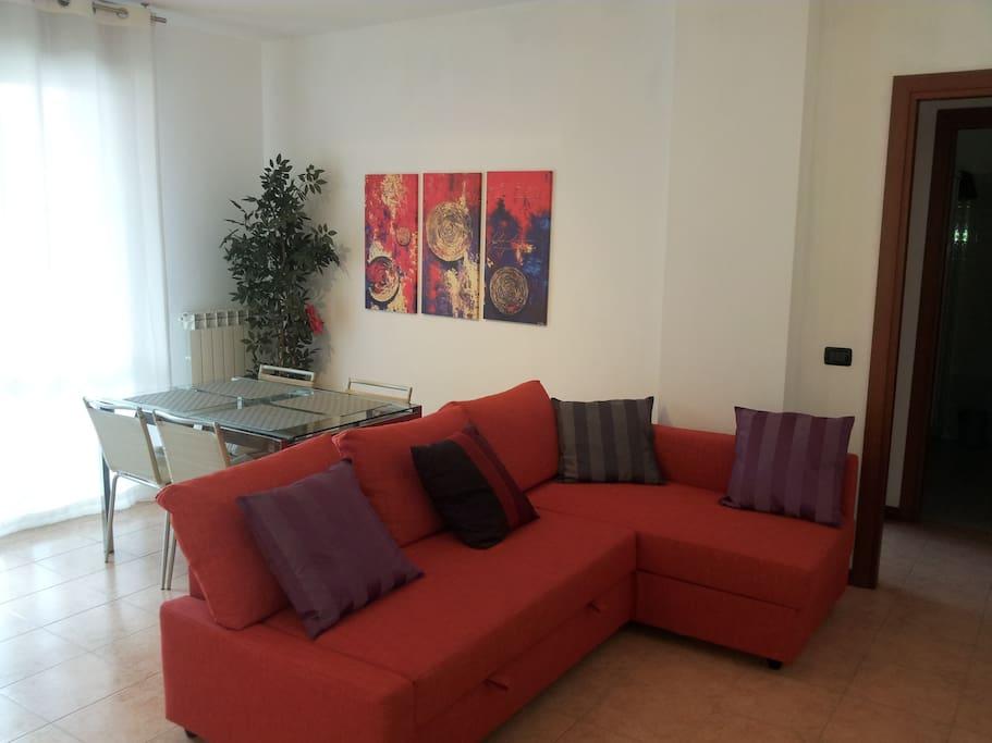 Living-room, table and double sofa bed. Soggiorno con tavolo e divano letto doppio.