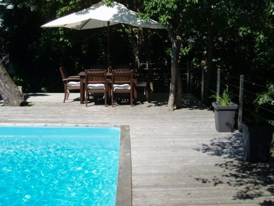 Comfortable back deck with lounge chairs, outside umbrella shaded table/chairs and solar heated pool