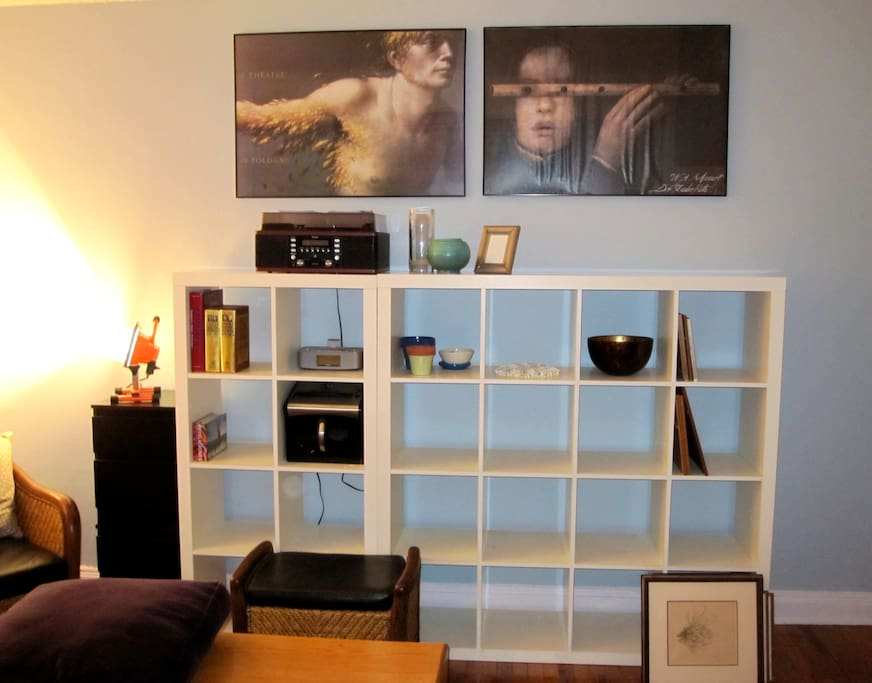 Facing wall with open shelves and art work.
