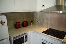 Kitchen with microwave, cook top and oven