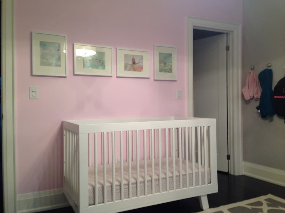 Baby room with full size crib, change table, glider, and sound machine