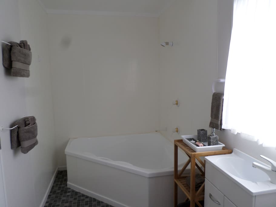 Own bathroom includes large bath with shower over bath.