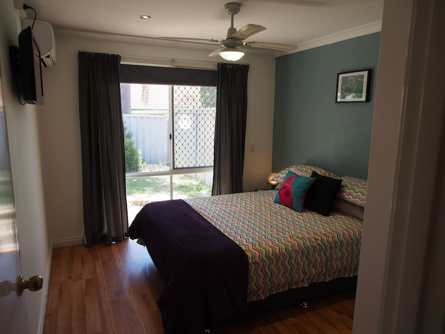 Second bedroom, with queen size bed,  TV, air con unit and double wardrobe
