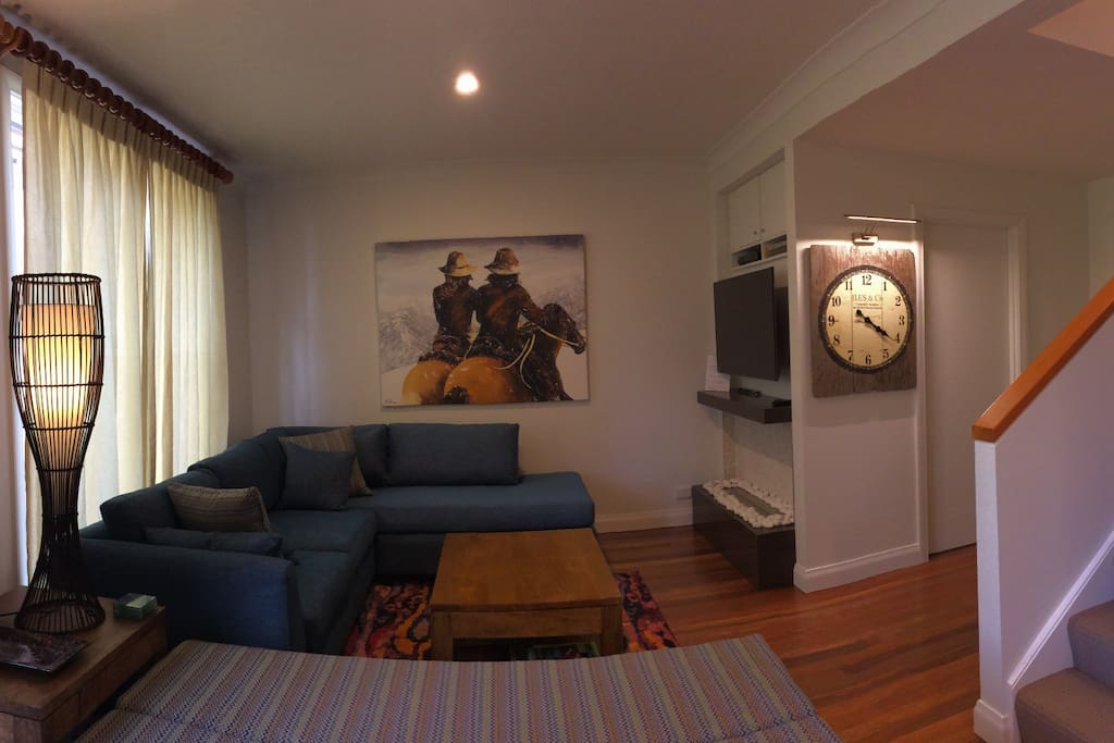 Lounge with open fireplace, large screen TV and sofa bed.