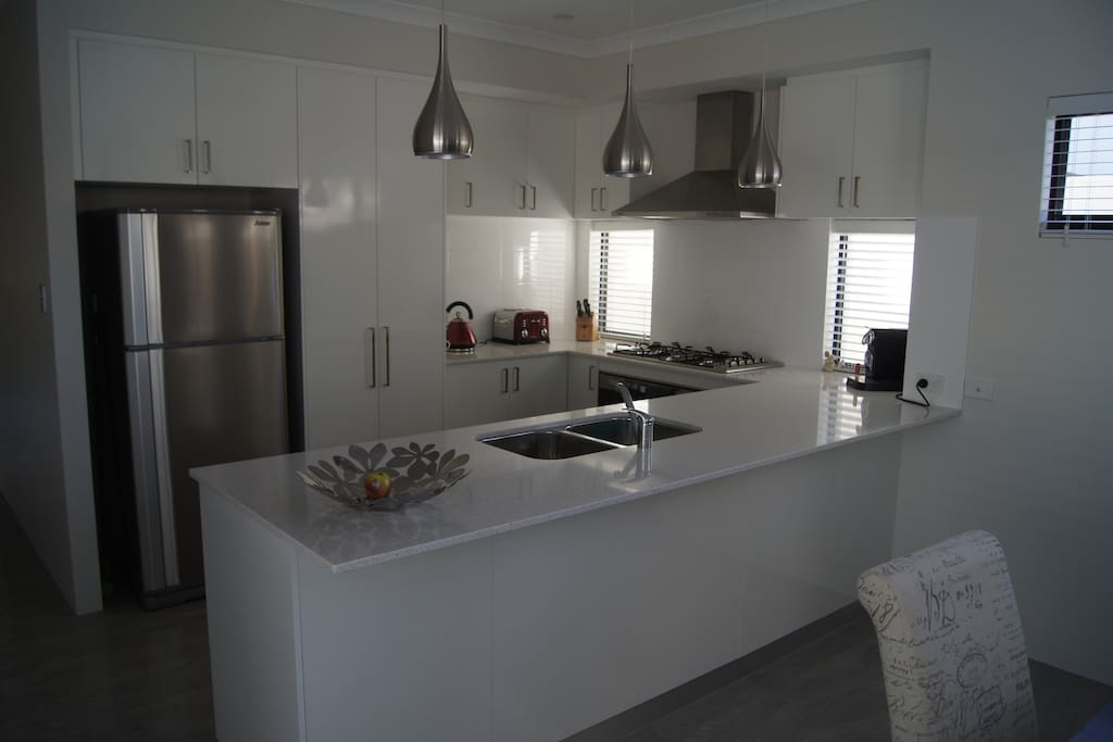 Modern kitchen with stainless steel appliances and stone bench tops