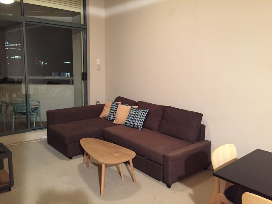 Comfy L-couch with access to the balcony overseeing the city lights.
