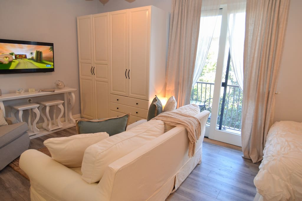 Large flat screen smart tv with Netflix capabilities can be viewed from the sofa and the bed