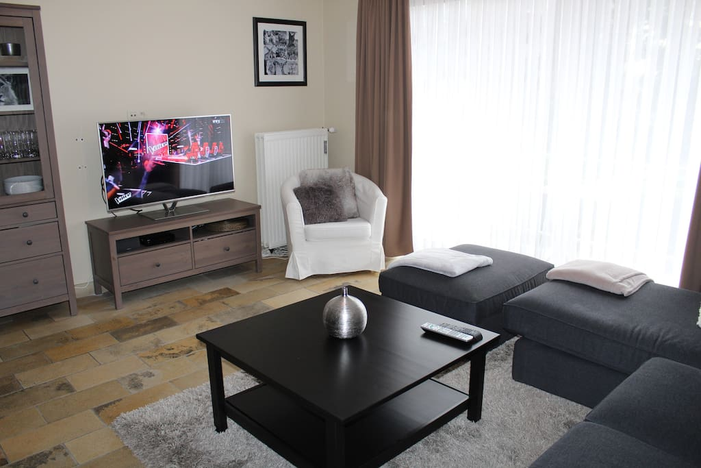 Large smart TV with lots of channels and door to the terrace.