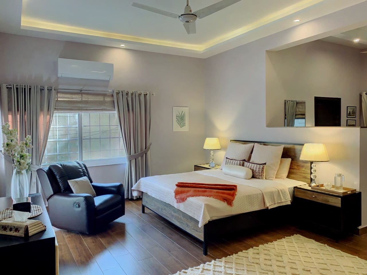 Master bedroom with king-size bed,  recliner, changing area.