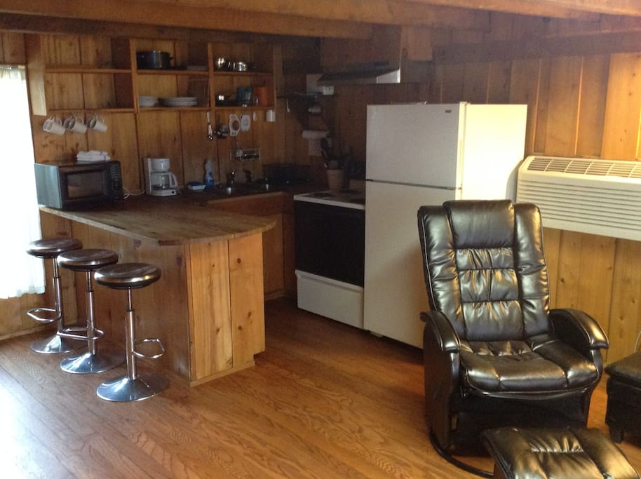 Downstairs view from living room into kitchen.  Has bar with barstools comes with microwave, coffee pot oven/stove and refrigerator and stocked with pots and pans glasses and silver ware.  Living room has a glider rocker and click-clack couch that can be