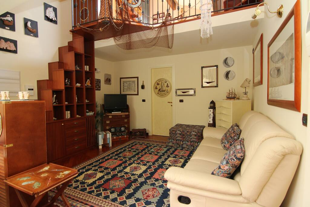 Soggiorno e scala verso la mansarda.  Living room and staircase to mansarda.