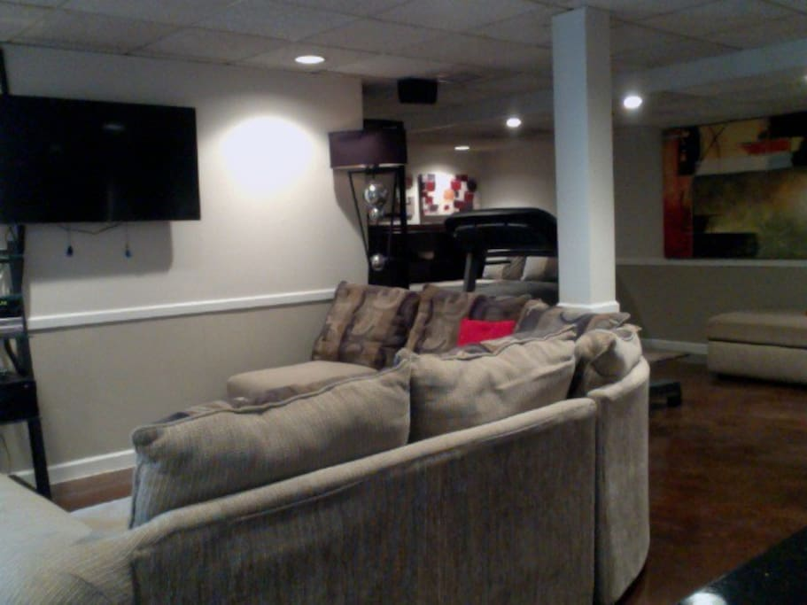 Spacious living area with flat screen cable TV and sectional couch.