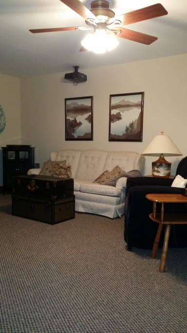 Large bedroom with couch, chair and queen bed
