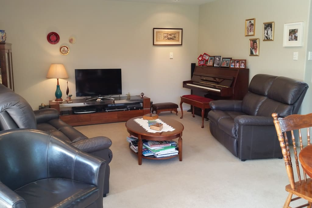 The lounge area with a 40 inch tv and a piano