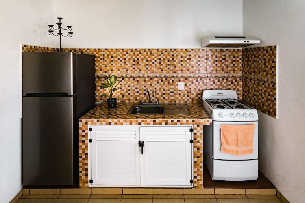 Full kitchen with stove, blender, fridge, kitchen utensils.