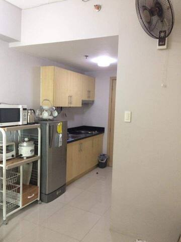 Kitchen with microwave, oven toaster, rice cooker, electric kettle.