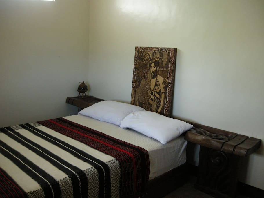 Double bed with a wooden headboard used as side table.