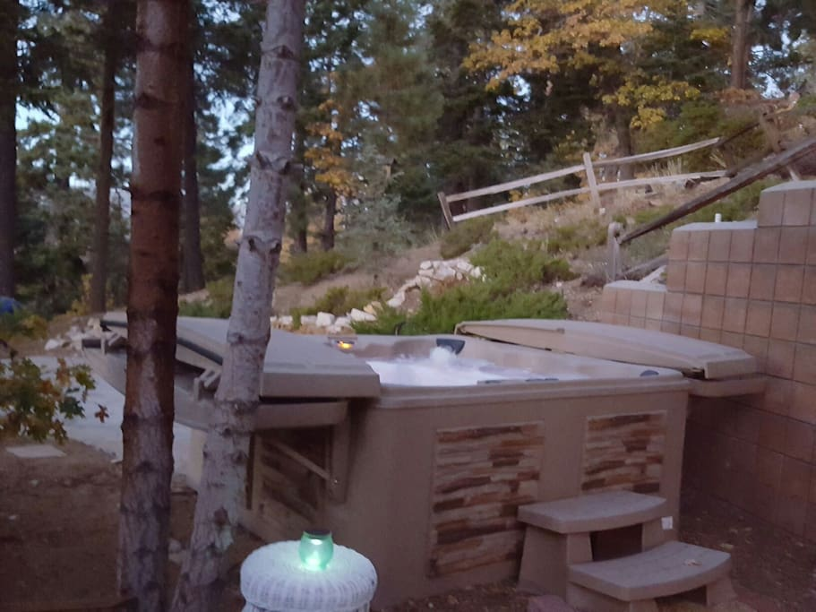 secluded hot tub looks out past the trees to the lake