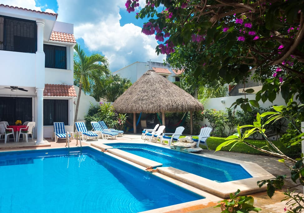 Looking across the 2 level pool toward the palapa roofed patio and garden