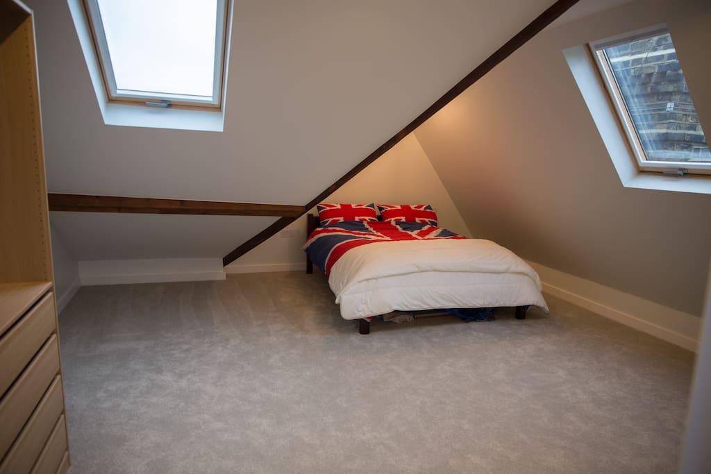 Huge open bedroom with skylights and wardrobe.