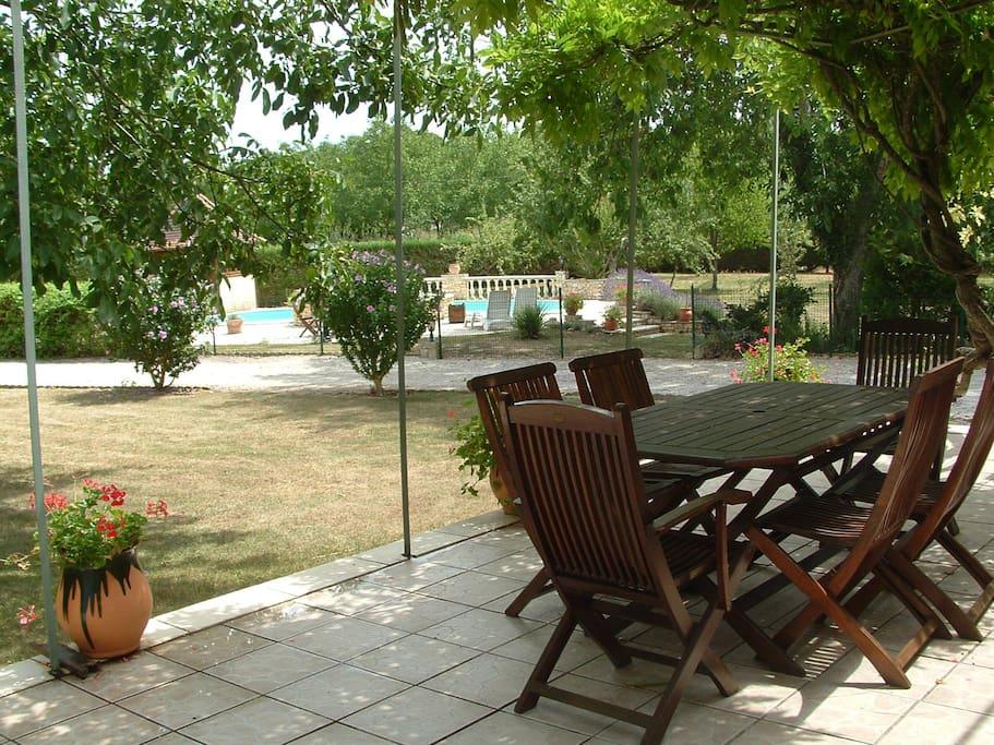 Jardin vu depuis l'une des terrasses de la maison ombragée sous une glycine