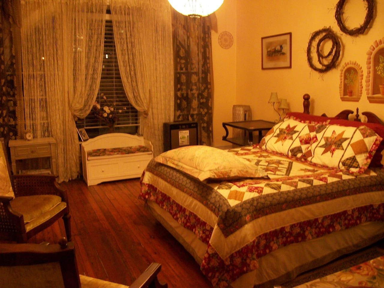 Main room, ueen size bed, desk, chairs, panoramic cathedral window overlooks small park