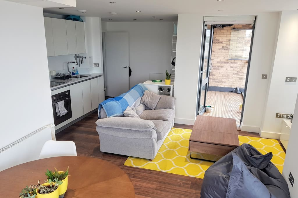 Bright living area and kitchen and you can see the smaller balcony in the back